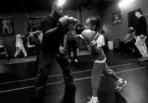 black and white photo of Khali and a young girl boxing