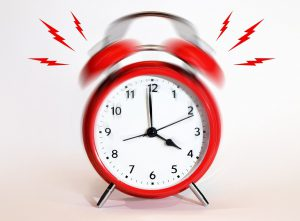 red alarm clock ringing with lightning bolts on each side of it