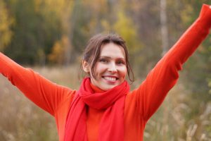 caucasian woman smiling with her hands up