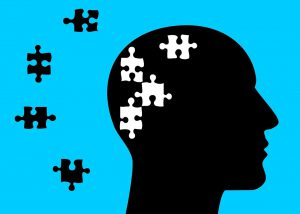 silhouette of a head with white puzzle pieces missing, and the black pieces outside of the head.