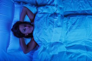 woman laying in bed awake with her hands behind her head