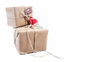 two boxes wrapped with string and a heart tag