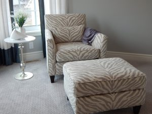 a chair and ottoman that is tan and white zebra print