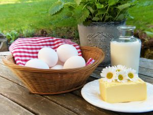 eggs in a basket, cheese, milk, and greens in a pot