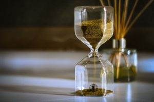 hourglass filled with sand on the top sprinkling down