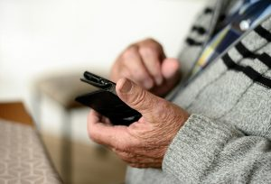 older looking hands holding a cell phone
