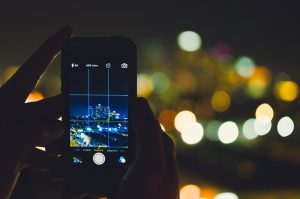 hands holding a cell phone taking a picture of the night skyline