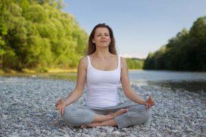older caucasian woman sitting on rocks and meditating
