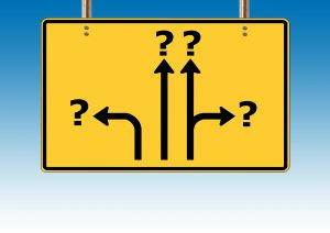 yellow sign with arrows and question marks at the end of the arrows