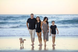 a family of four walking on the beach smiling