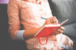 woman's torso sitting down writing in a red journal