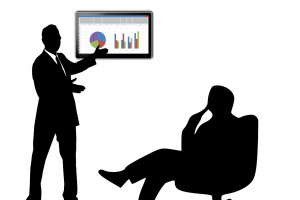person sitting down and another person standing up pointing towards a screen with graphs on it