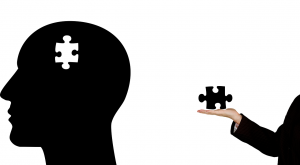 silhouette of a head with a white puzzle piece missing and a person's hand holding the puzzle piece