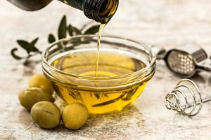 olive oil in a glass dish with olives on the side of the dish