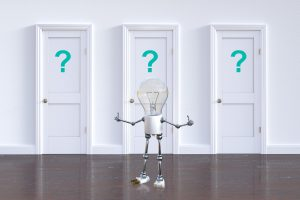 light bulb standing in front of 3 white doors with blue question marks on them