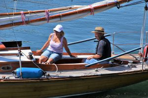 two older people sitting on a boat in the sun