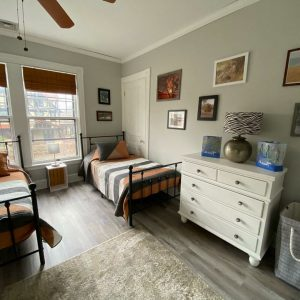 room with 2 beds in it and a dresser