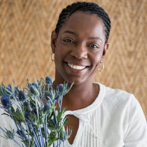 African American woman holding thistle smiling